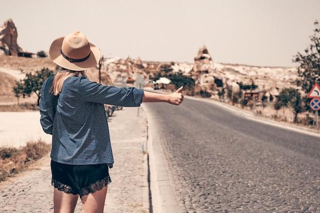 道端に立つ麦わら帽子の一人のヒッチハイカーの女の子