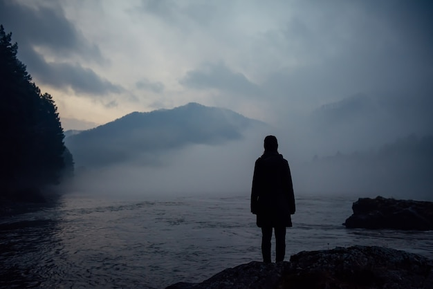 Alone human silhouette in white haze against the mountains and river. thick fog in the evening twilight. mysterious atmosphere. reflection, meditation.