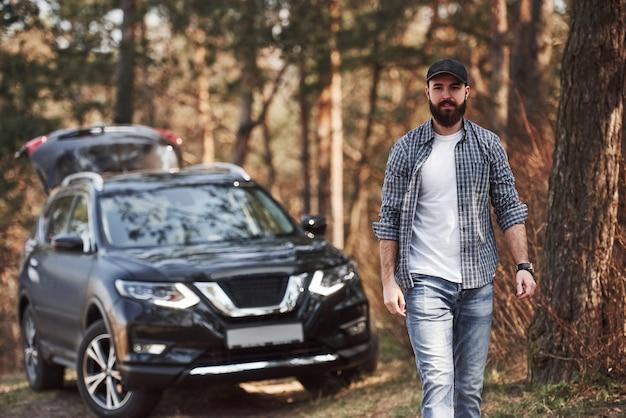 森の中で一人で。森の中の彼の真新しい黒い車の近くのひげを生やした男。休暇の概念