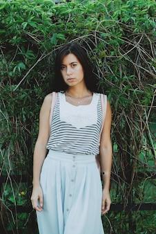 Alone inspired girl walks in garden among summer greenery