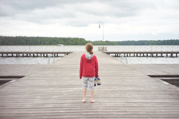 Alone kid stands on pier backwards and observing waterscape