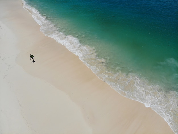 Alone men walk on the beach in summer with sea waves  clear and beautiful color top view by drone