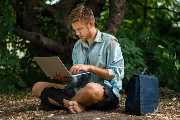 Alone office worker with laptop on desert island. business risk, collapse or bankruptcy concept