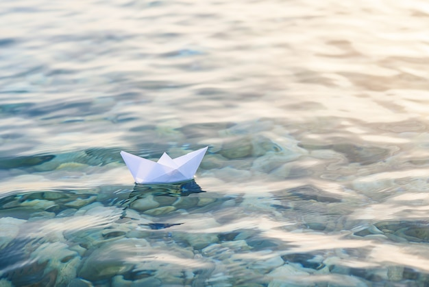 Alone paper boat floats in waves on the water.