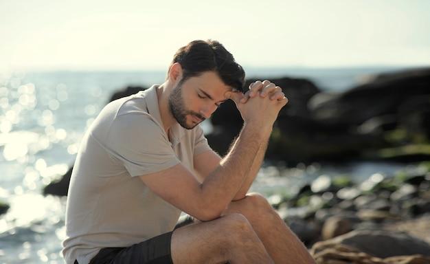 Alone sad man sitting on beach