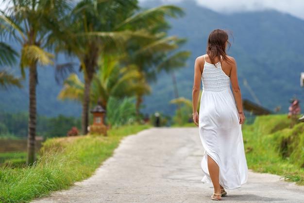 Одинокая загорелая девушка в белом платье идет вперед по дороге.