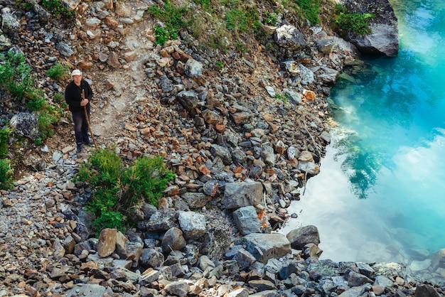 Один путешественник с деревянной ручкой на тропе около ясного лазурного горного озера. походы в горы. путь среди камней в удивительной горной местности. богатая растительность величественной горной природы. вид сверху.