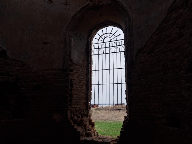 Одно окно с решеткой в темном старом здании с видом на поле