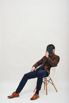 Наедине с книгой стильный мужчина, сидящий на стуле, изолированные на белом фоне