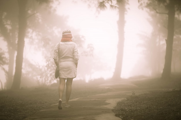 Alone woman walking in the misty forest with foggy