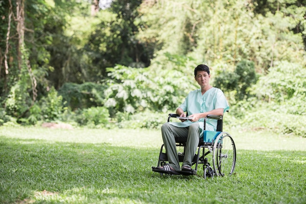 Alone young disabled man in wheelchair at the garden