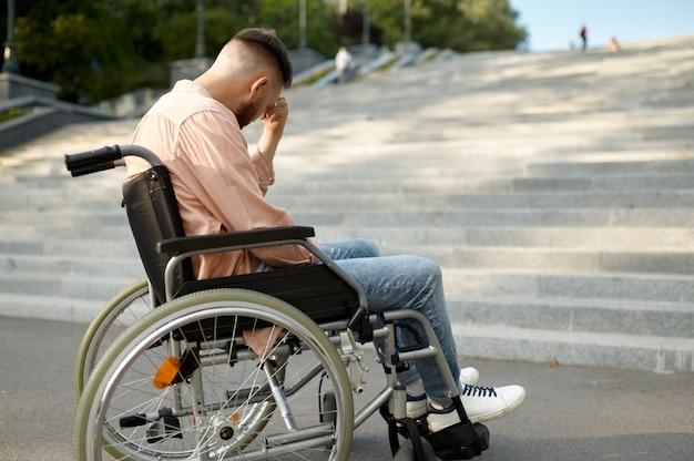 階段で車椅子の若い男だけ、ハンディキャップの問題。麻痺した人と障害、ハンディキャップの克服。公園を歩いている無力な障害者男性