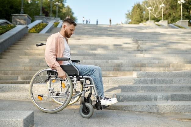 계단에서 휠체어를 탄 혼자 젊은 남자, 무력하고 장애가 있는 문제. 마비된 사람들과 장애 어려움, 장애 극복. 공원에서 걷는 장애인 남성