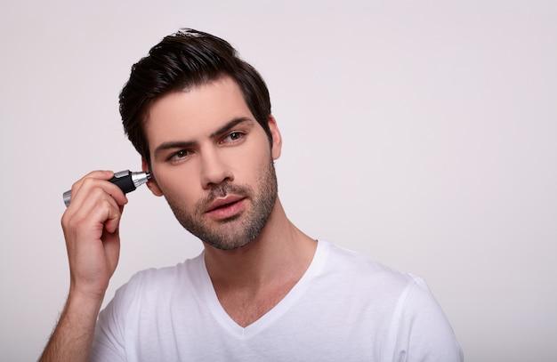 若い白人の男が彼のaloneのスラムマーで髪を削除します。