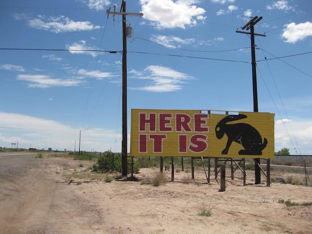 사막 길을 따라 노란색 광고판 표지판은 토끼 실루엣이 있는 here it is라고 읽습니다.