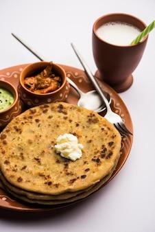Aloo paratha 또는 인도 감자 속을 채운 플랫브레드 위에 버터를 얹습니다. 신선하고 달콤한 라씨, 처트니, 피클과 함께 제공됩니다. 선택적 초점