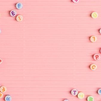 Alphabet beads border pink background