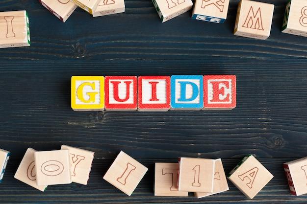 Алфавит преграждает abc на деревянном столе. текст - путеводитель.