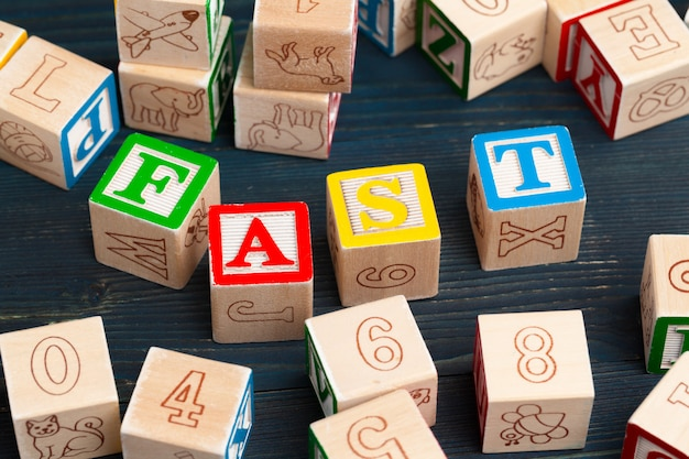 Alphabet blocks abc on wooden table. text - fast