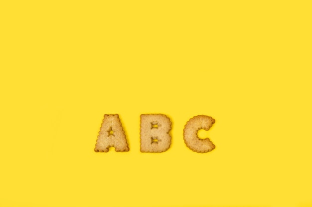 Alphabet cookies letters on a yellow background with copy space