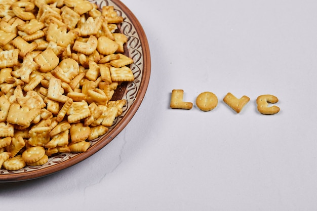 Alphabet crackers on a ceramic plate and word love spelled with crackers.