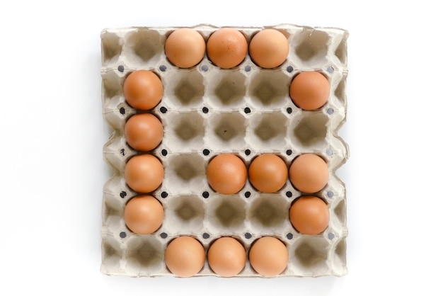 Alphabet letters arrange from eggs in paper tray on white background.