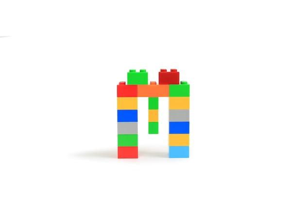 흰색 배경에 고립 된 다채로운 플라스틱 벽돌 블록 생성자에서 알파벳 문자 m
