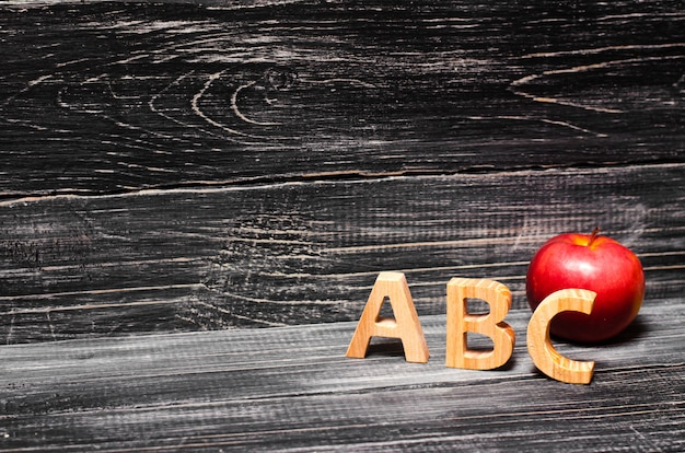 Alphabet letters and red apple on a black background