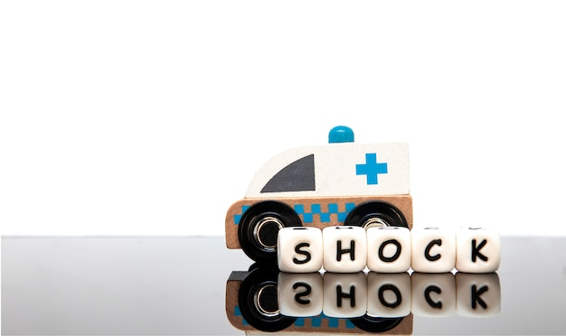 Alphabet letters spelling the word shock and a toy ambulance