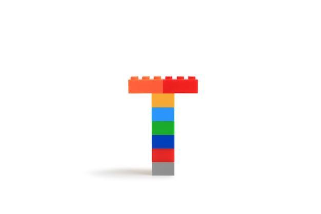 Буквы алфавита t из красочного пластикового кирпичного блока конструктора, изолированные на белом фоне