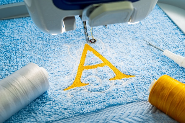 Alphabet logo design on towel in hoop of embroidery machine