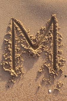 해변의 모래에 손으로 쓴 알파벳(m) 글자