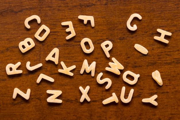 Alphabet made of macaroni letters isolated on wood background.