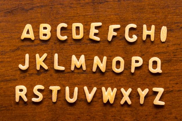 木の背景に分離されたマカロニ文字で作られたアルファベット。