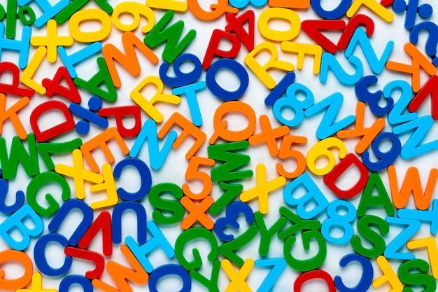アルファベット、プラスチックの数字と文字で多色の背景。 abc。教育の概念。標識とカラフルな抽象的なテクスチャ。知識のシンボル。色のパターン。