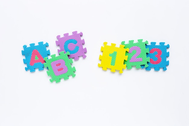 Alphabet puzzle with number puzzle on white.