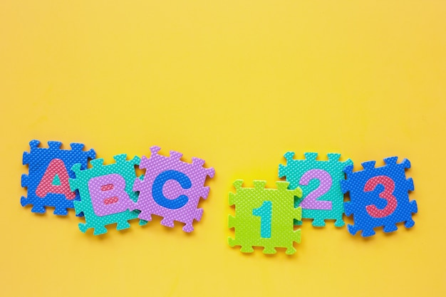 Alphabet puzzle with number puzzle on yellow copyspace