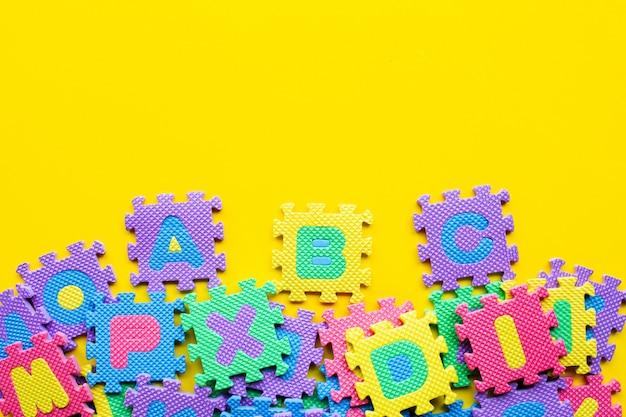 Alphabet puzzle on yellow.