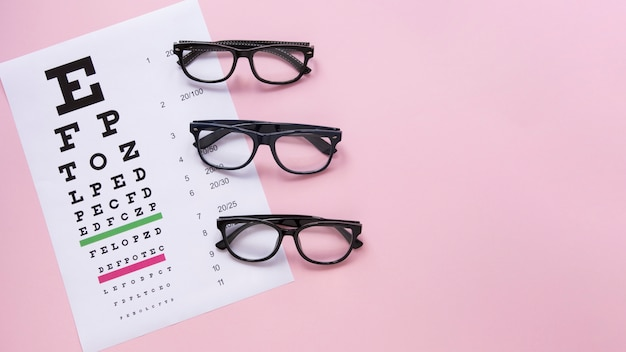 Alphabet table with glasses on pink background