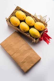 알폰소 망고는 잔디 위에 선물 상자에 넣고 빨간 리본으로 묶고 선택적인 초점