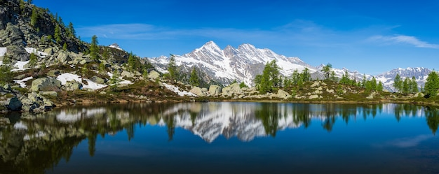 Alpine lake in idyllic environment with rocks and forest