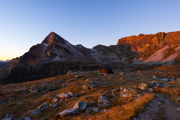 Alpine meadow and pasture set amid high altitude mountain range at sunset