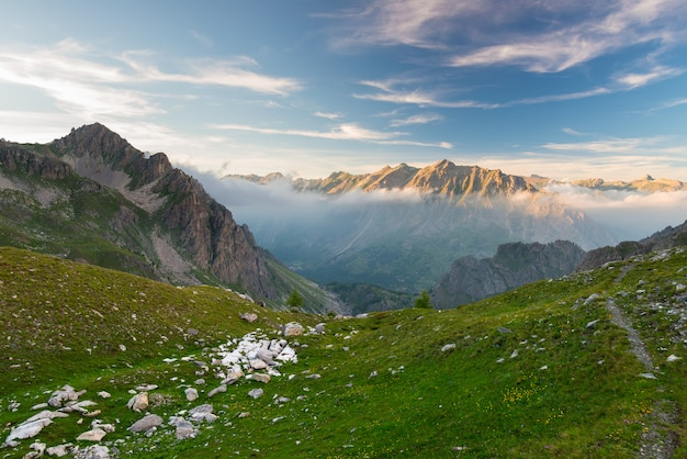 Alpine meadow and pasture set amid high altitude mountain range at sunsets