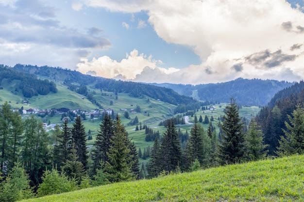 夕方の空の下の高山の牧草地と丘
