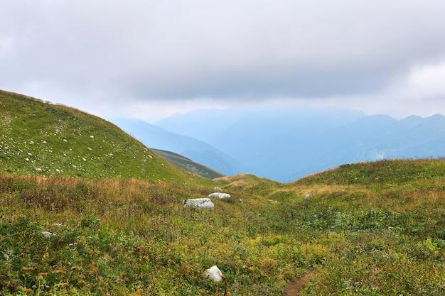 안개 낀 계곡이 내려다보이는 흐린 가을 날 코카서스 산맥의 고산 초원