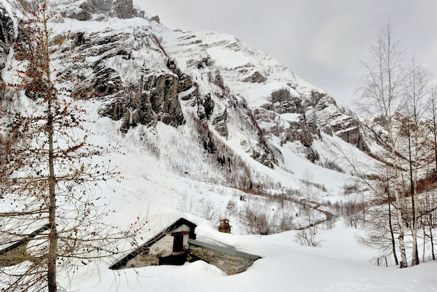 雪に埋もれたシャレーと雪の中のアルプスの山