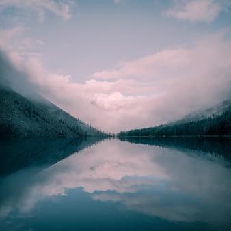 早朝の霧と高山の神秘的な自然の正方形の背景。濃霧の中の山の湖に沿って丘の中腹にある先のとがったモミの頂上のシルエット。穏やかな水の中の針葉樹の反射。