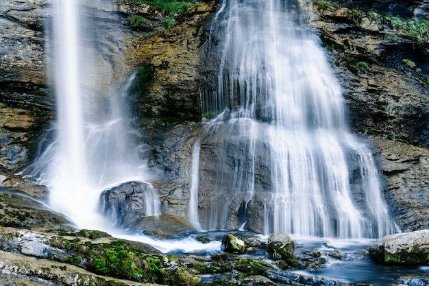Alpine scenic mountain waterfall landscape covered with green glass, rocks.