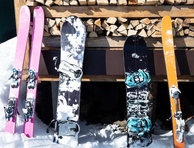 Горнолыжные лыжи и сплитборды на деревянной стене спортивное снаряжение для скитура