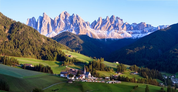 Alpine village with dolomites mountains on background